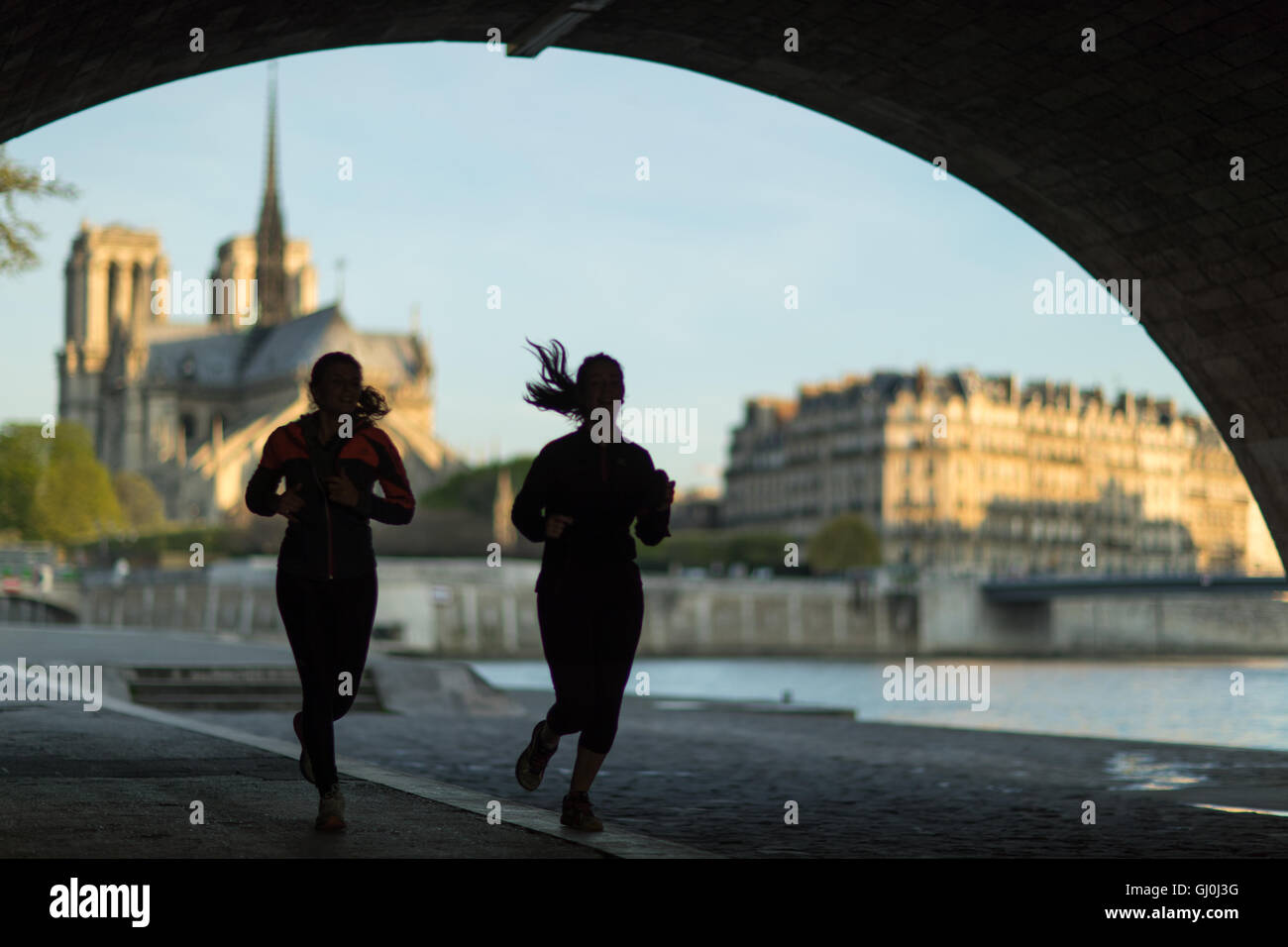 joggers running under the Pont de la Tournelle on the left bank of the River Seine, Paris, France - Stock Image