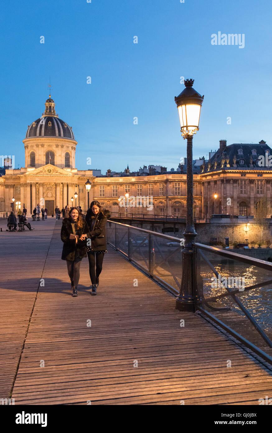 Figures on Pont des Arts at dusk, Paris, France - Stock Image
