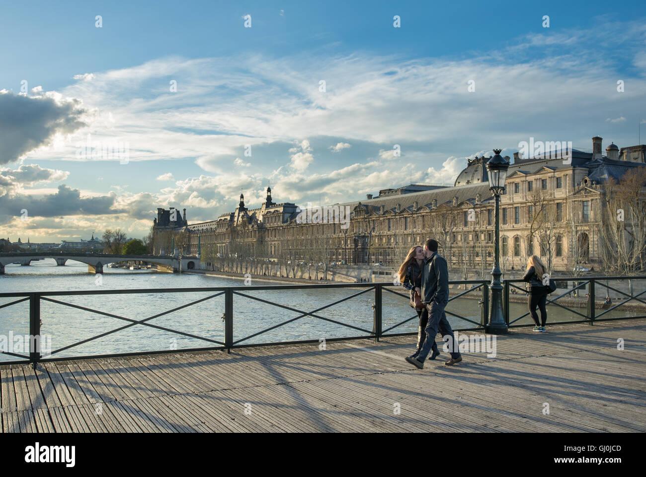 a couple kissing on the Pont des Arts over the River Seine with the Palais du Louvre, Paris, France - Stock Image