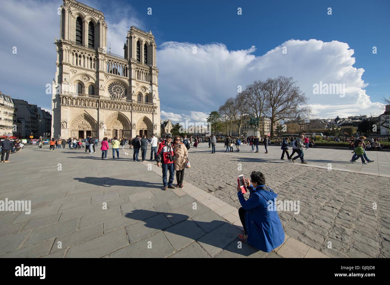 tourists taking photos in front of Cathedrale Notre Dame, Île de la Cité, Paris, France - Stock Image