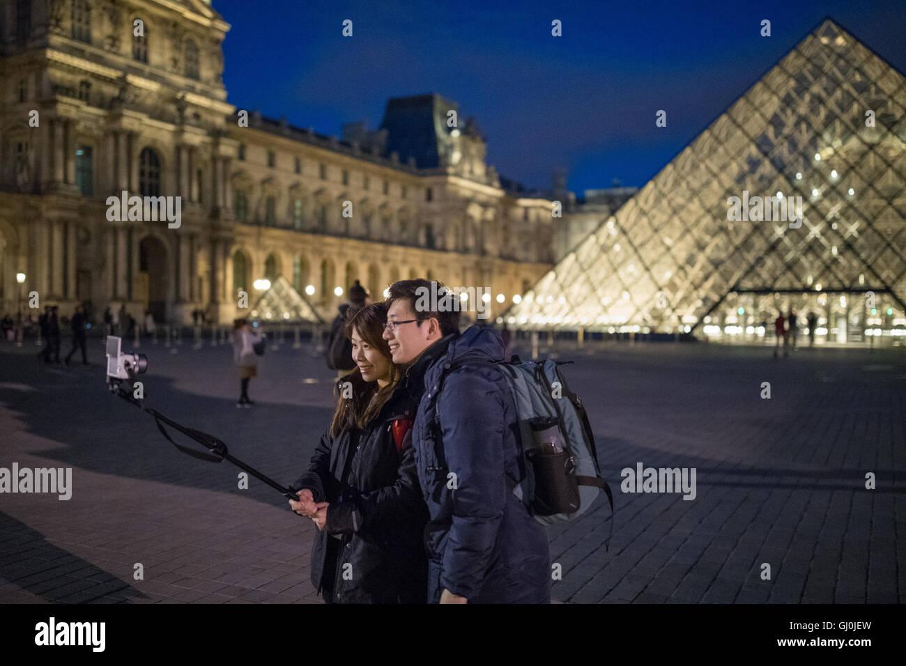 tourists taking  a Selfie at the Palais du Louvre at dusk, Paris, France - Stock Image
