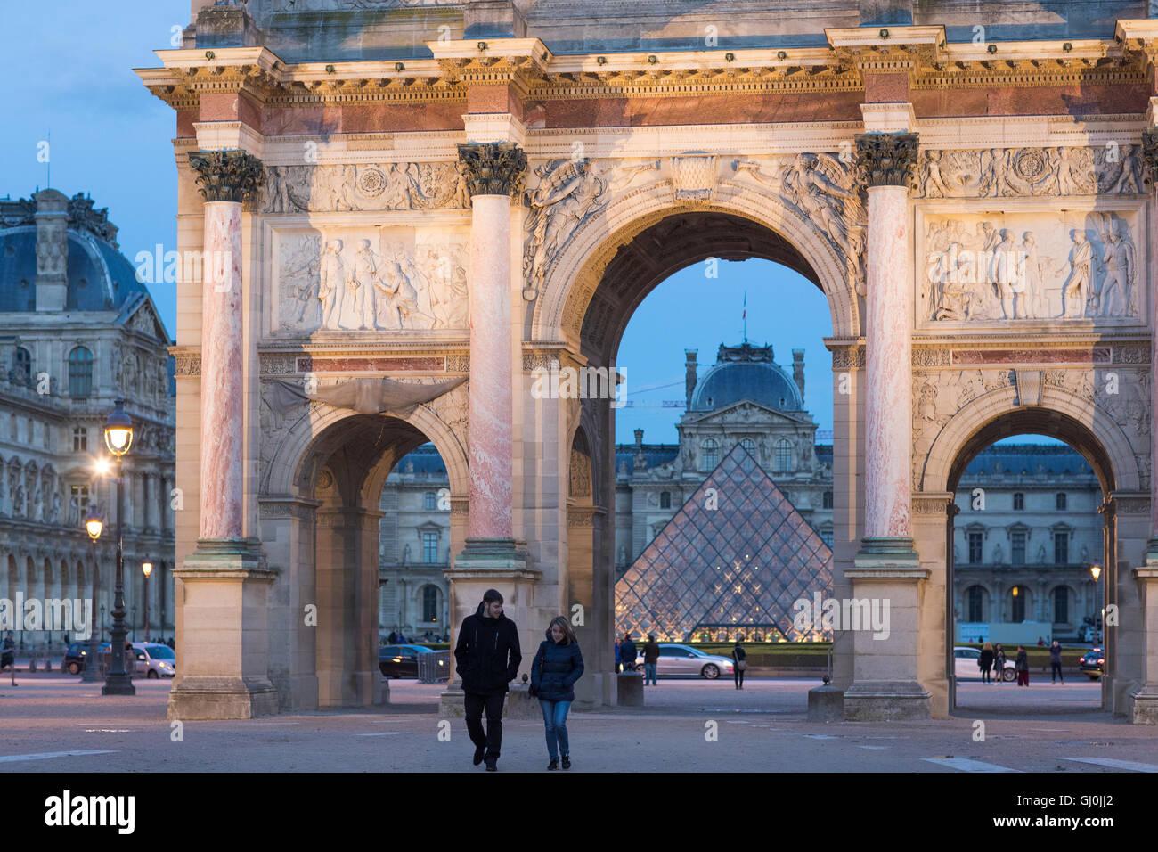 a couple strolling by the Arc de Triomphe du Carrousel & Palais du Louvre at dusk, Paris, France - Stock Image