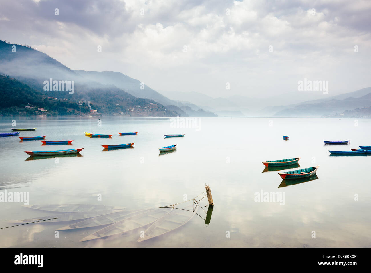 Boats on Phewa Lake in Pokhara, three sunken ones in the foreground, Nepal. - Stock Image