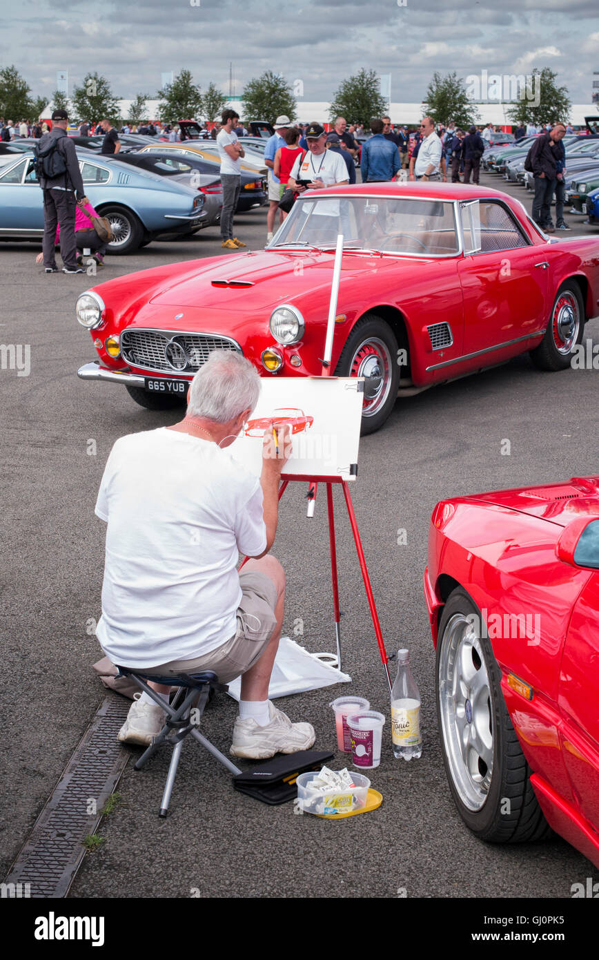 Man painting a vintage Maserati car at the Silverstone Classic event. UK - Stock Image