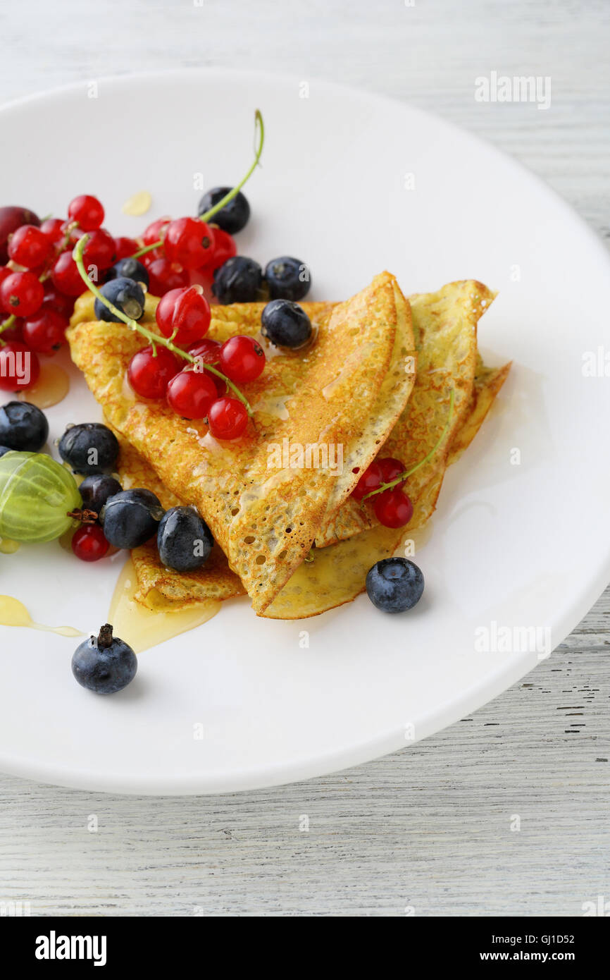 Hot pancake with sauce and berries. Food close-up - Stock Image