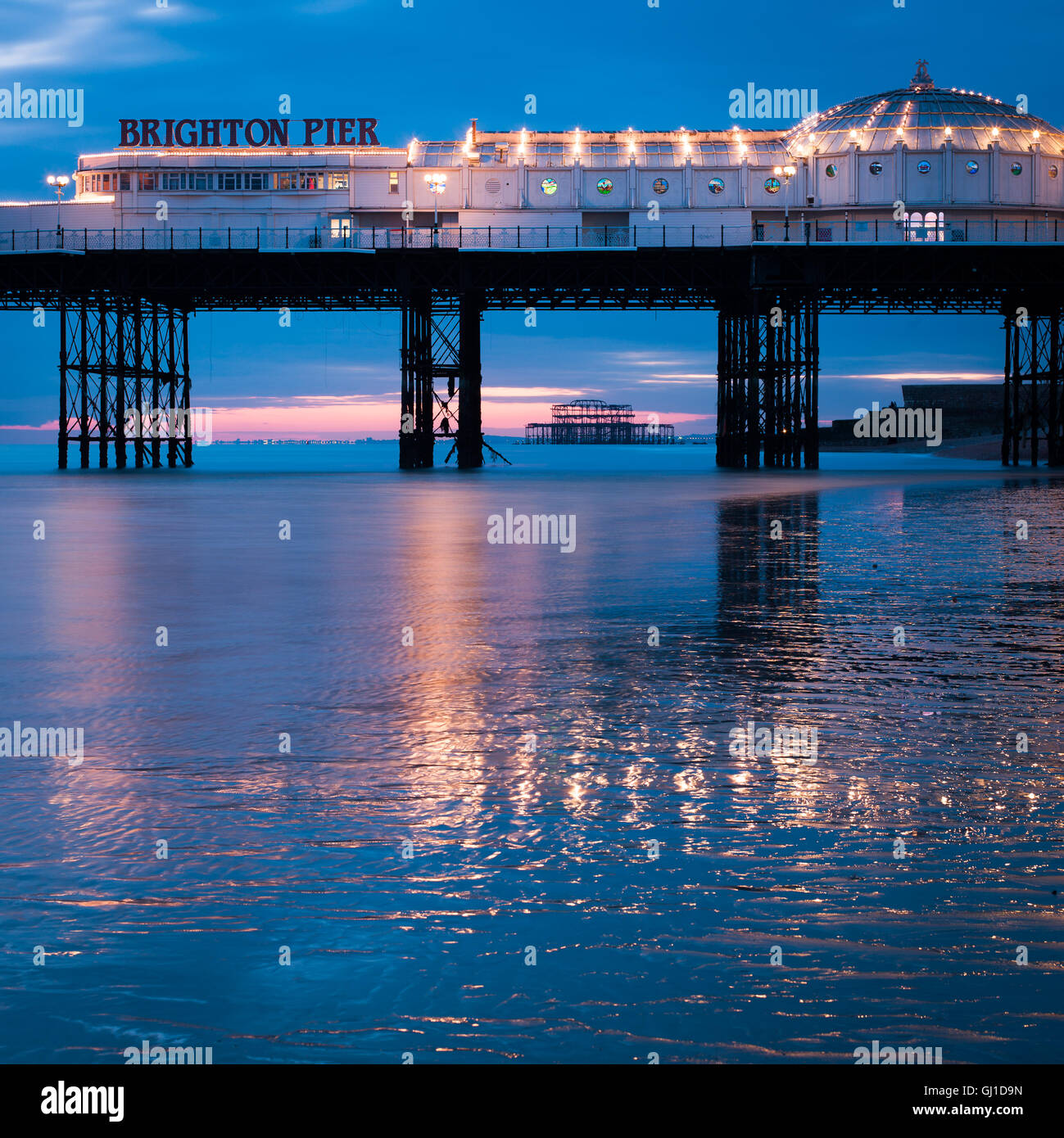 Brighton Pier at dusk reflects in the wet sands of low tide. In the distance the old West Pier can be seen. - Stock Image