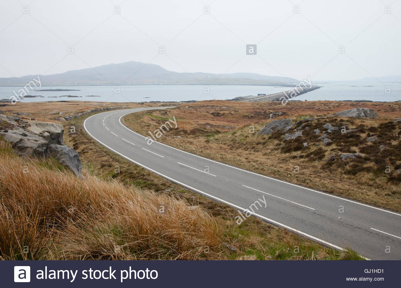 An empty road leading to the causeway connecting South Uist to Eriskay, Outer Hebrides, Scotland. Stock Photo