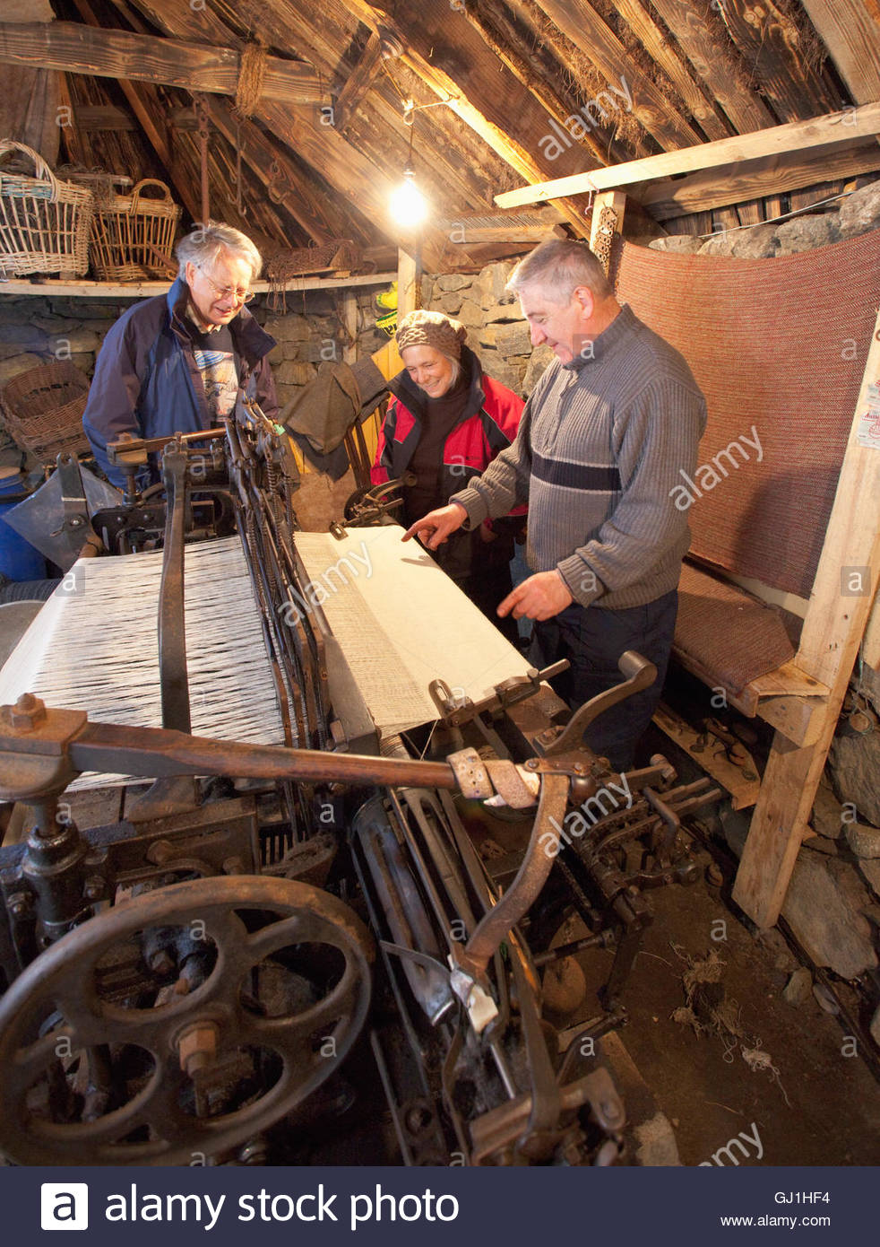 A weaver demonstrates a loom to two visitors at the Gearrannan Blackhouse Village, Carloway, Isle of Lewis, Outer Stock Photo