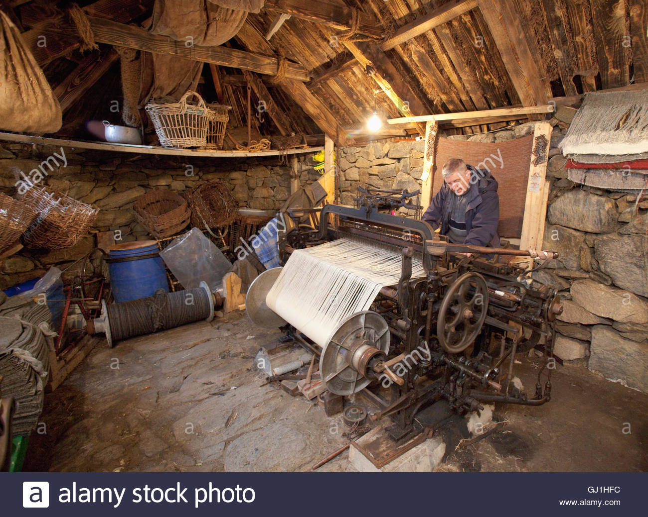 A weaver demonstrates a loom at the Gearrannan Blackhouse Village, Carloway, Isle of Lewis, Outer Hebrides. Scotland. - Stock Image