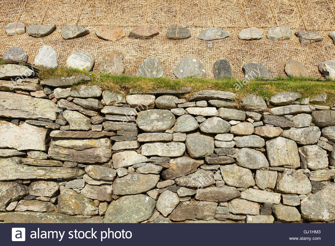 A detail of the rocks and netting holding down the thatch of the Blackhouse, Arnol, Isle of Lewis, Outer Hebrides. Stock Photo