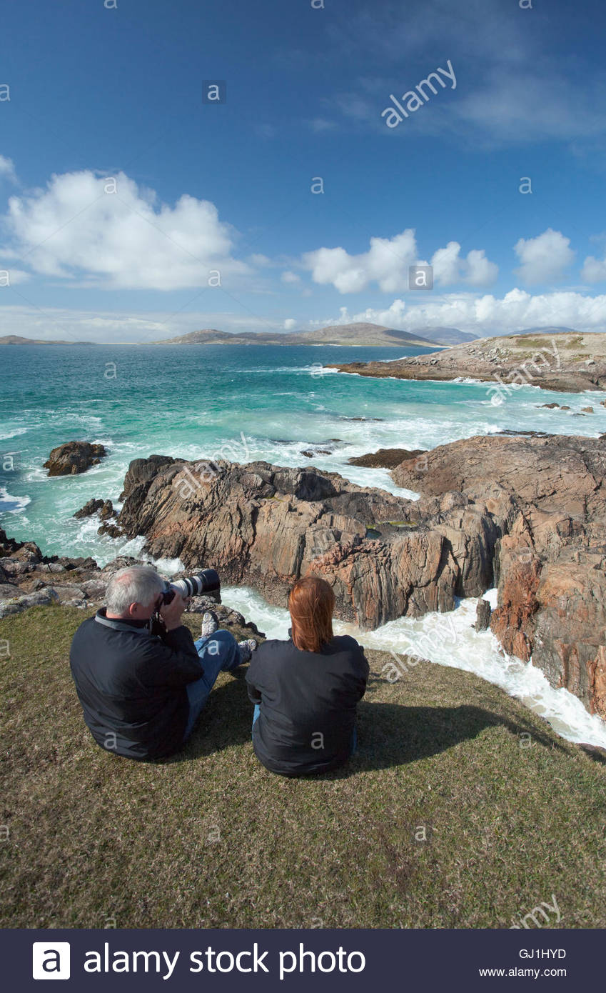 A couple taking in the view of the coast near Horgabost, Isle of Harris, Outer Hebrides, Scotland. - Stock Image