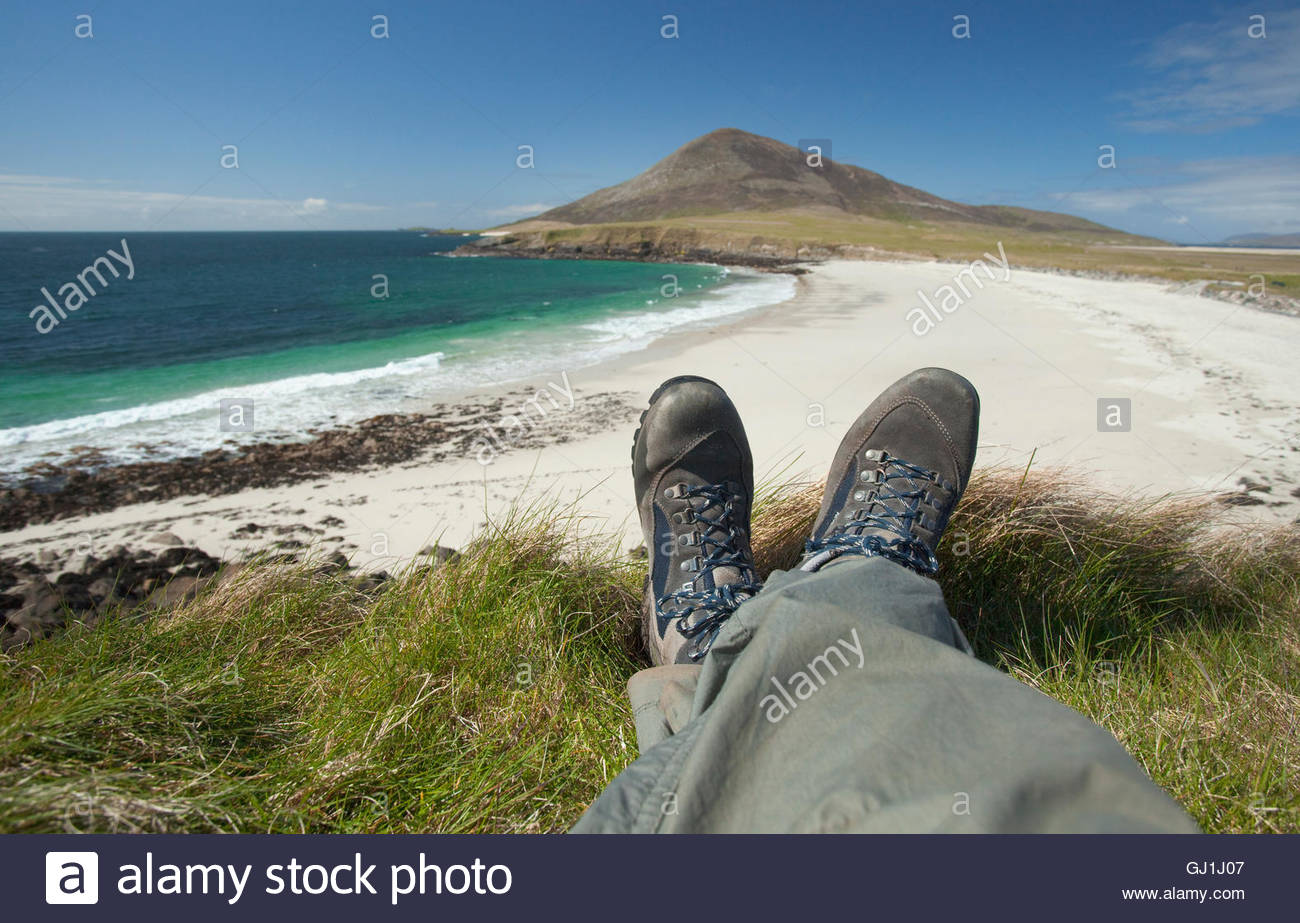 The feet of a walker as he lies by the empty white beach at Northton, Isle of Harris, Outer Hebrides, Scotland - Stock Image