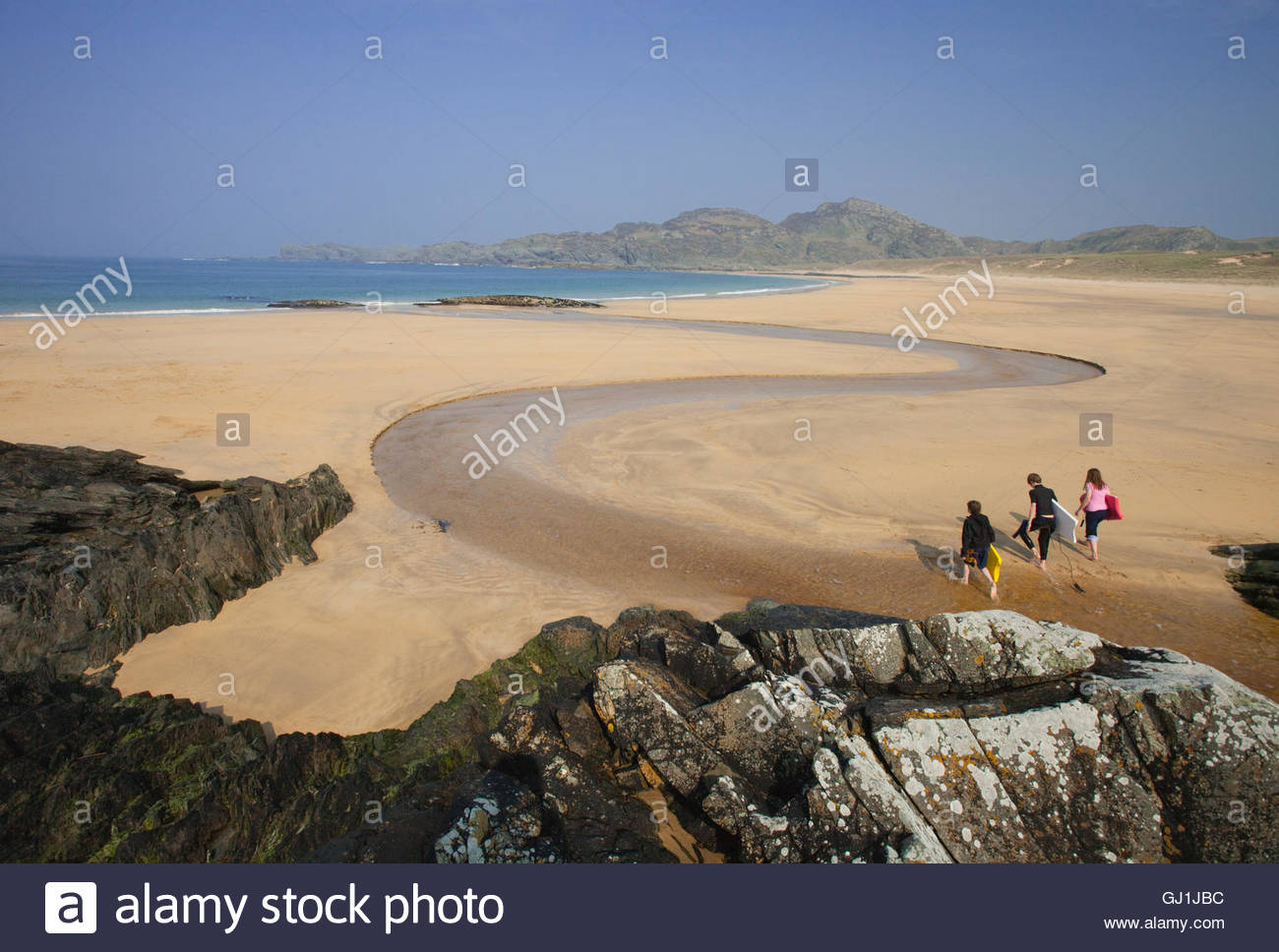 Children bodyboarding at Kiloran Bay, Isle of Colonsay, Inner Hebrides, Scotland. - Stock Image