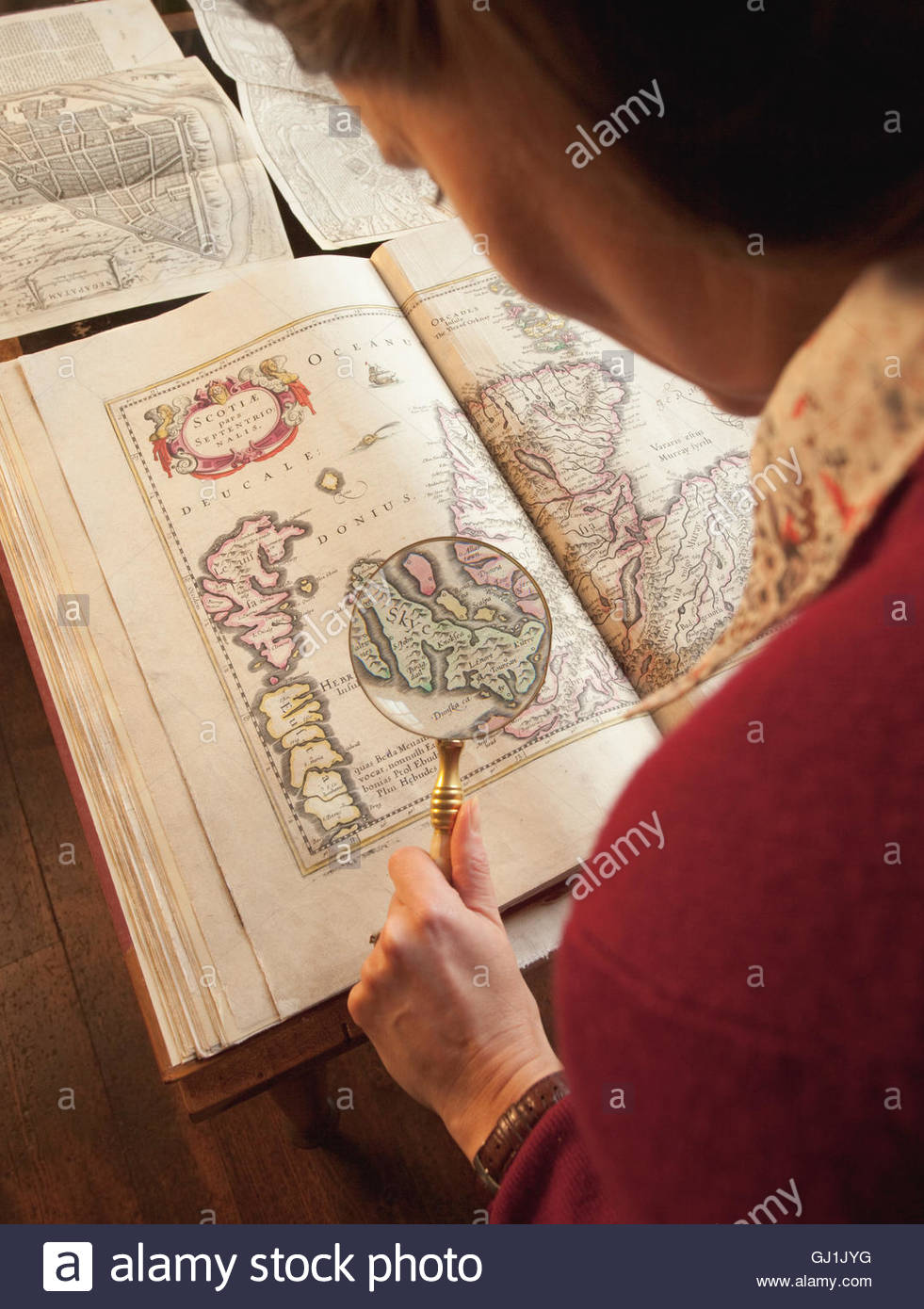 Examining an antique map with a magnifying glass at the Innerpeffray Library - Scotland's first free Public - Stock Image