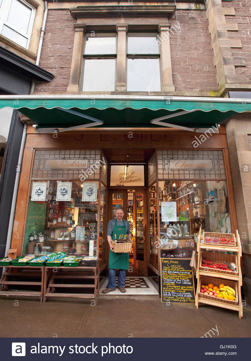 The shopkeeper poses for a photograph at J. L. Gill's speciality food shop, Crieff, Perthshire, Scotland. - Stock Image
