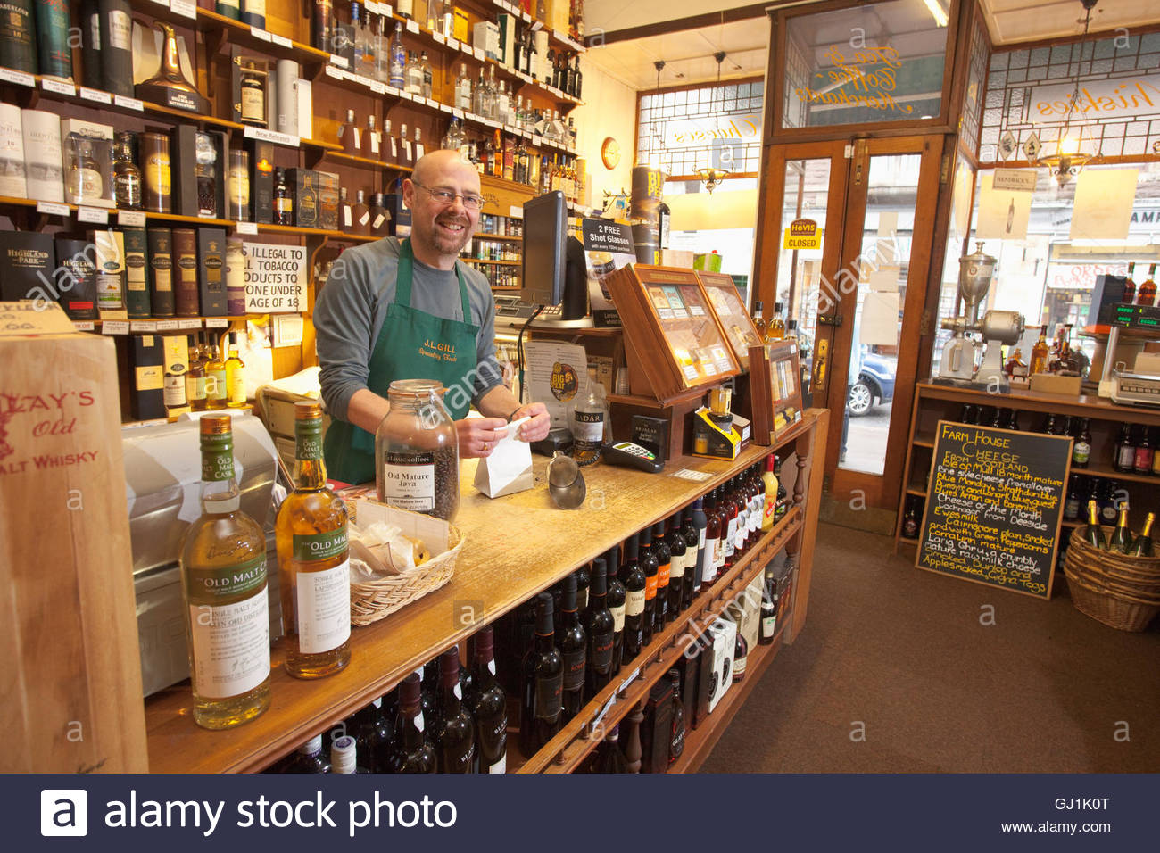 The shopkeeper measuring out coffee at J. L. Gill's speciality food shop, Crieff, Perthshire, Scotland. - Stock Image