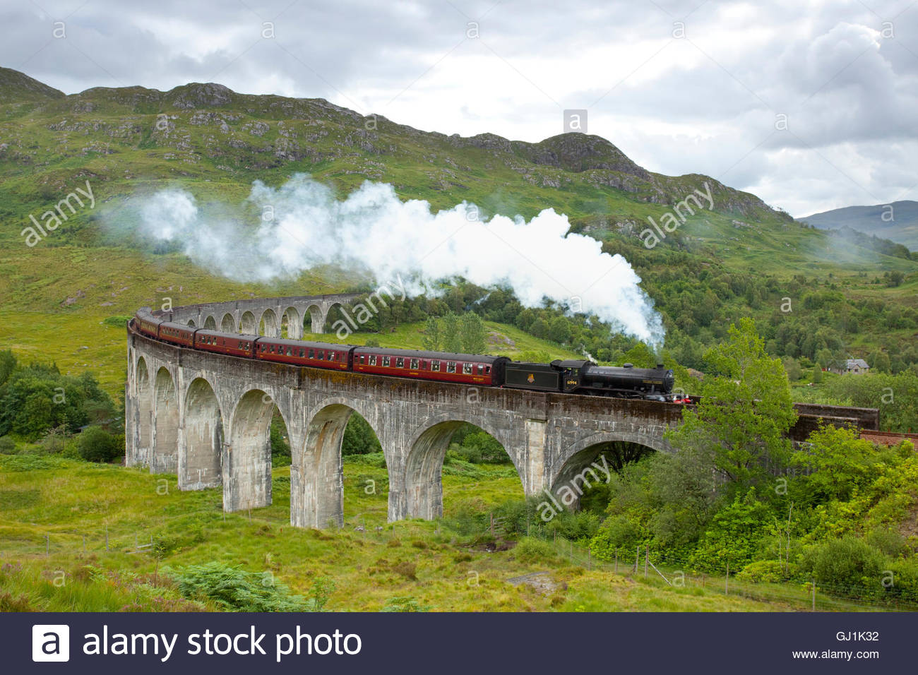 The Jacobite steam train passing over the Glenfinnan Viaduct, Lochaber, Highlands of Scotland. Stock Photo
