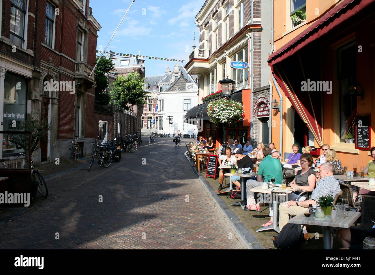Old and young people sitting at a terrace (De Drie Vrienden) on Wed Street, central Utrecht, The Netherlands - Stock Image