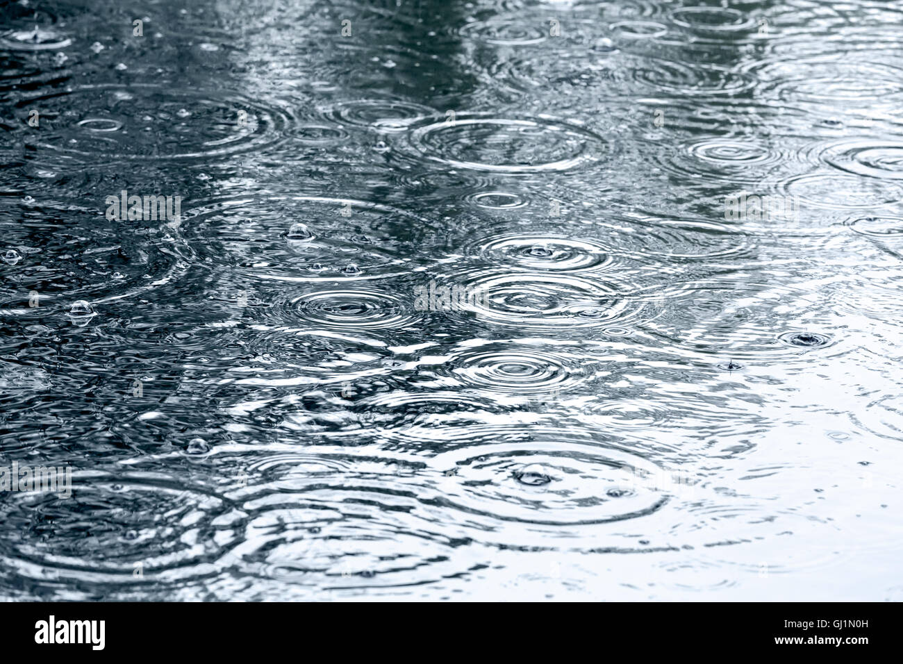 sidewalk with rain drops and ripples in puddles - Stock Image