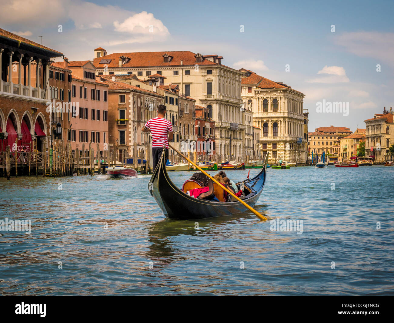 Gondola on the Grand Canal, with gondolier wearing a traditional striped top. Venice. Italy. - Stock Image