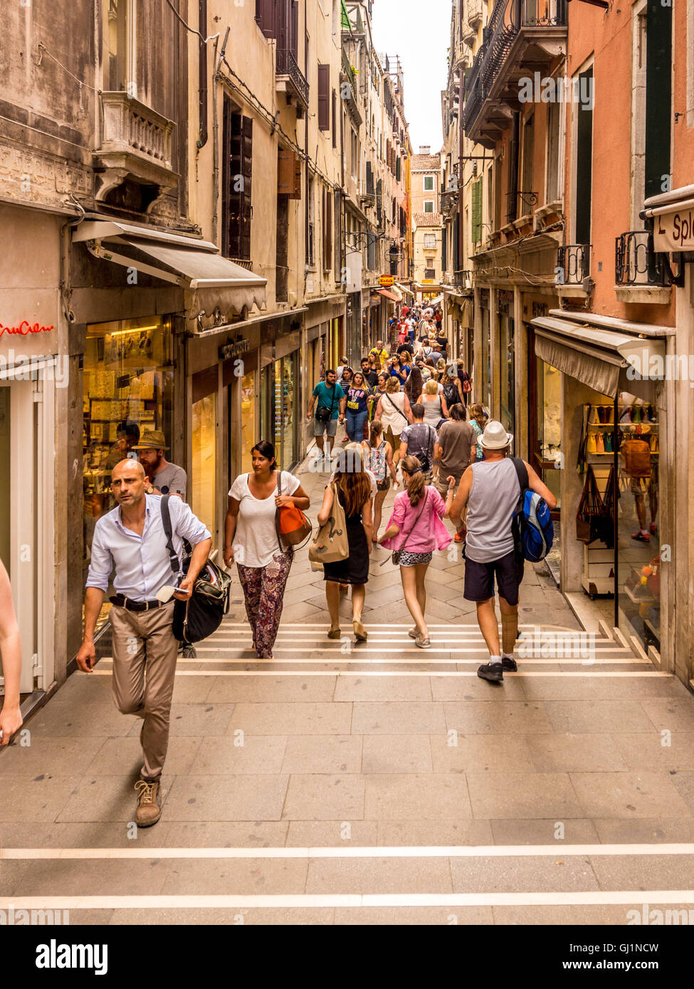 Tourists and shoppers in a narrow street in Venice, Italy. - Stock Image