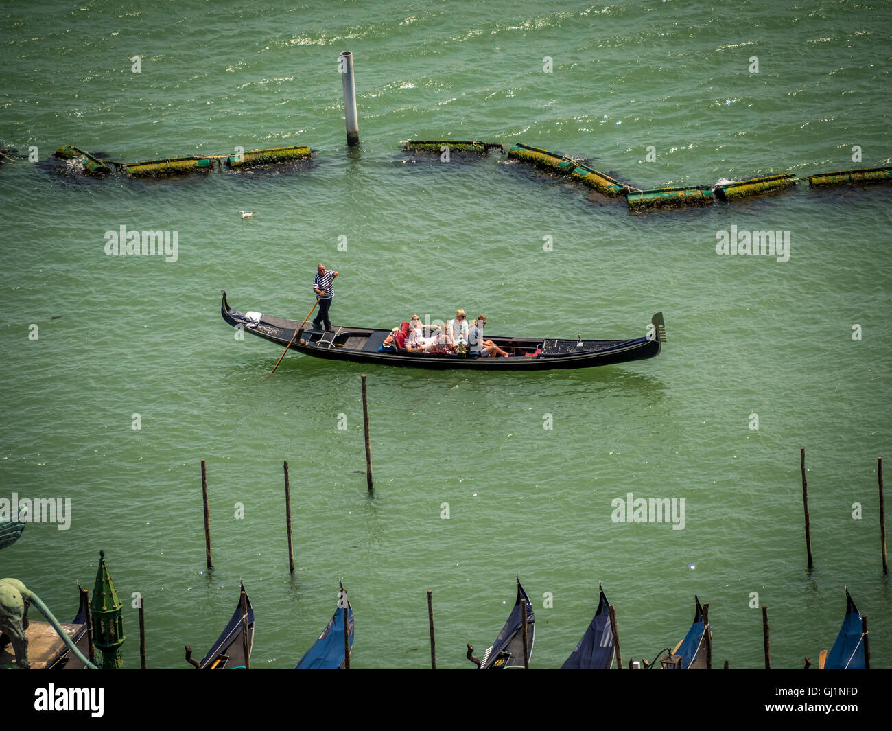 Gondola with gondolier and passengers in St Mark's Basin, Venice, Italy. - Stock Image