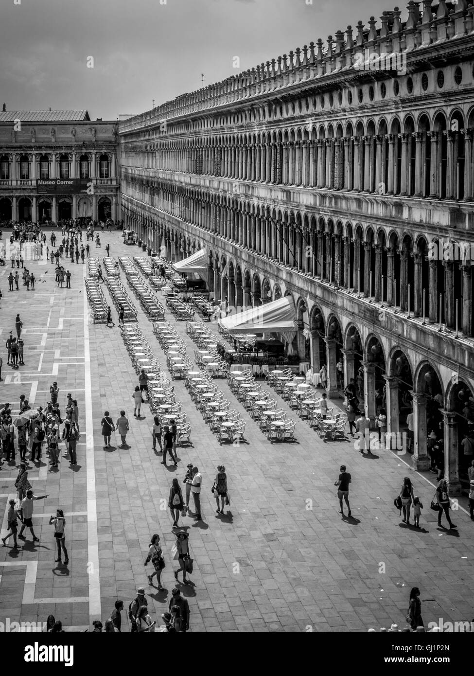 Aerial view of St Mark's square with people sitting at the cafe tables and chairs. Venice, Italy. - Stock Image