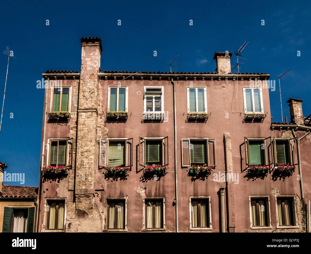 Traditional venetian rendered building. with window boxes and venetian blinds. Venice, Italy. - Stock Image