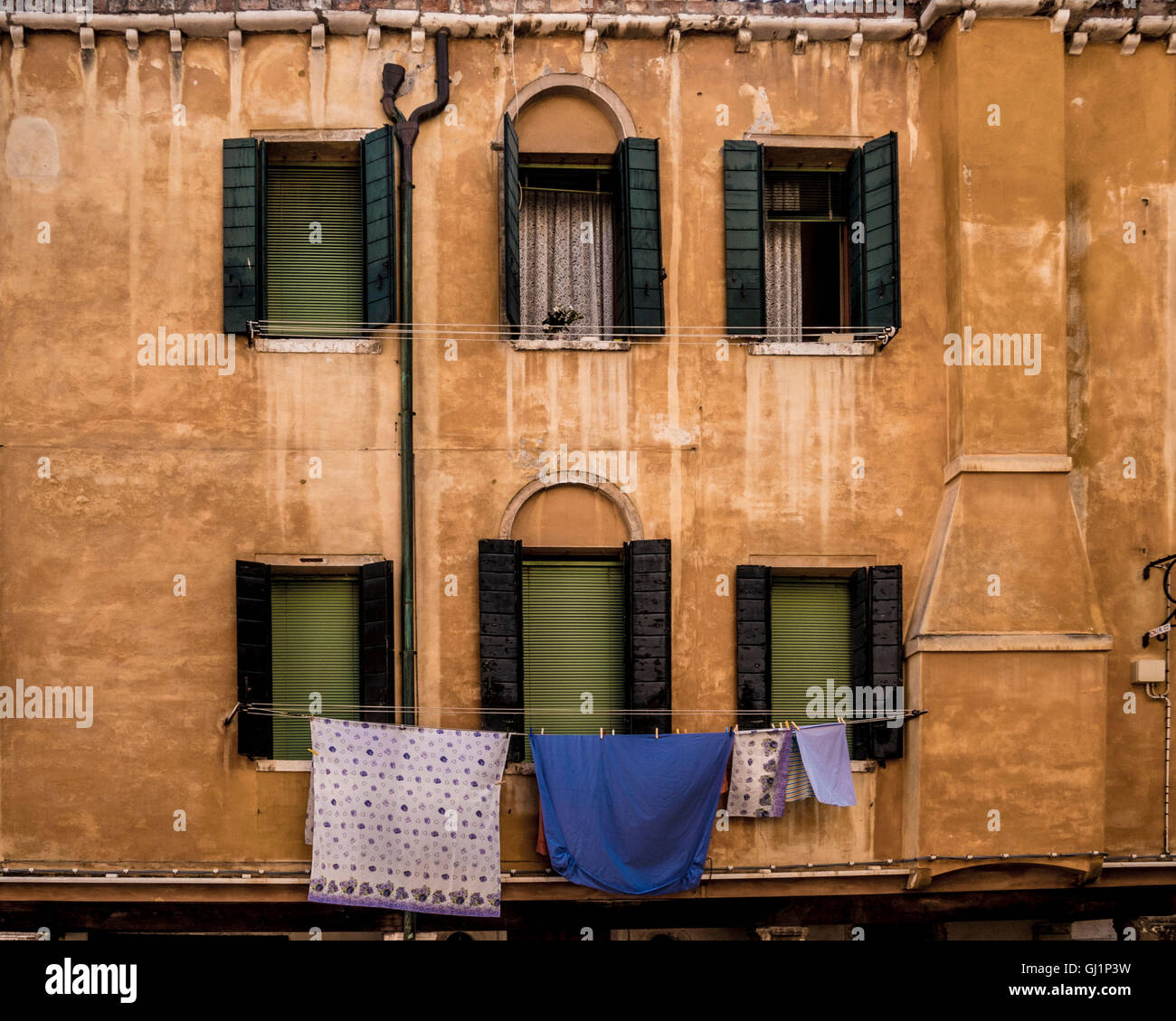 Traditional venetian rendered building. with window shutters, venetian blinds. and laundry hanging from a washing - Stock Image