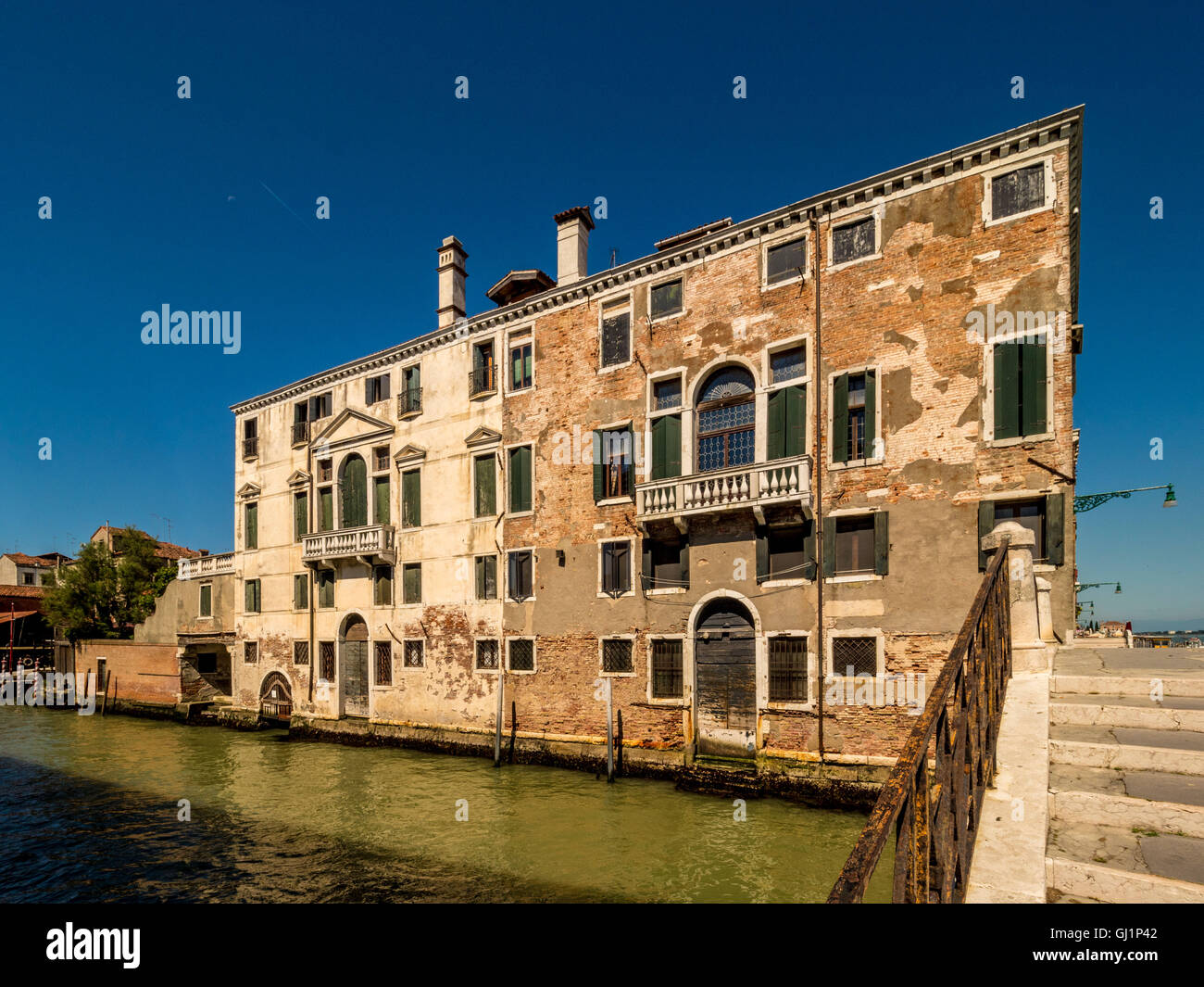 Traditional canal side building, with missing render and exposed bricks. Venice, Italy. - Stock Image