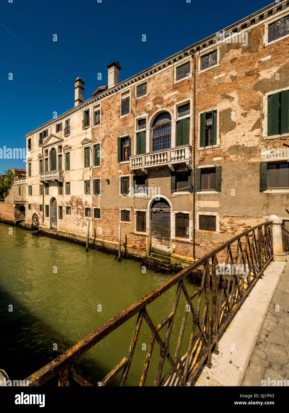 Traditional canal side building, with flaky rendering and exposed bricks. Venice, Italy. - Stock Image