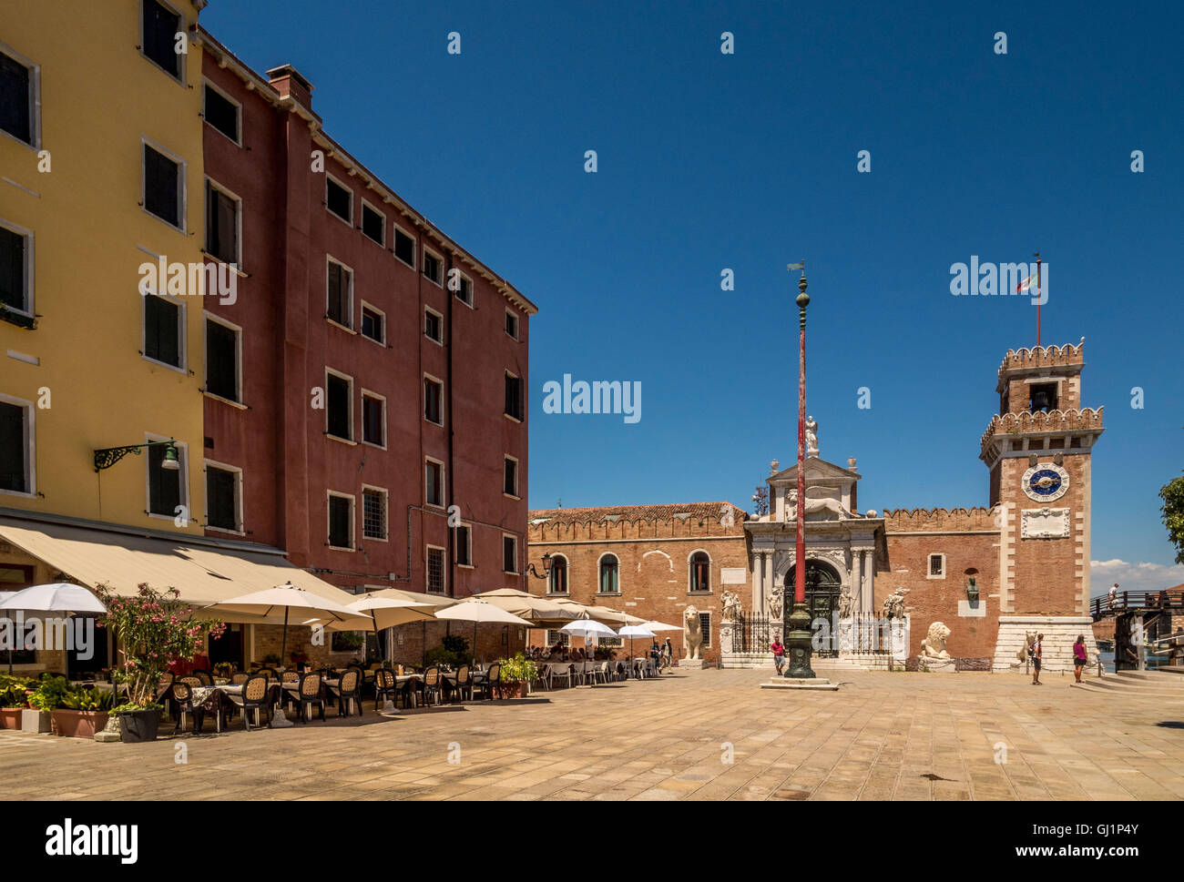 Canal side Cafe with Porta Magna, Arsenale in the background. Venice, Italy. - Stock Image