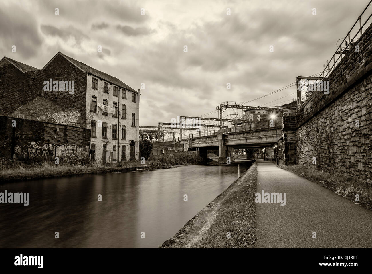 Dusk shot of the River Aire in Leeds City Centre with the train tracks in the background - Stock Image