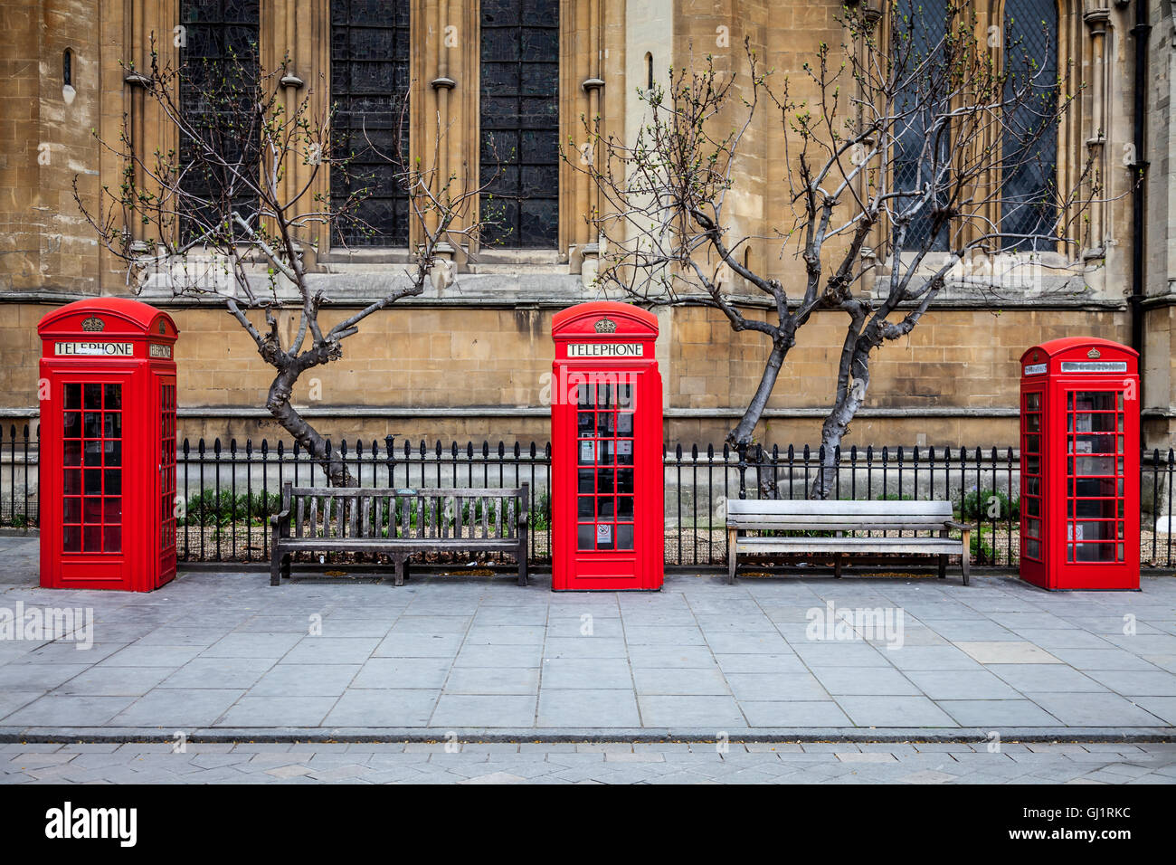 Three British red telephone boxes in front of a church. Bare trees and benches between them. - Stock Image