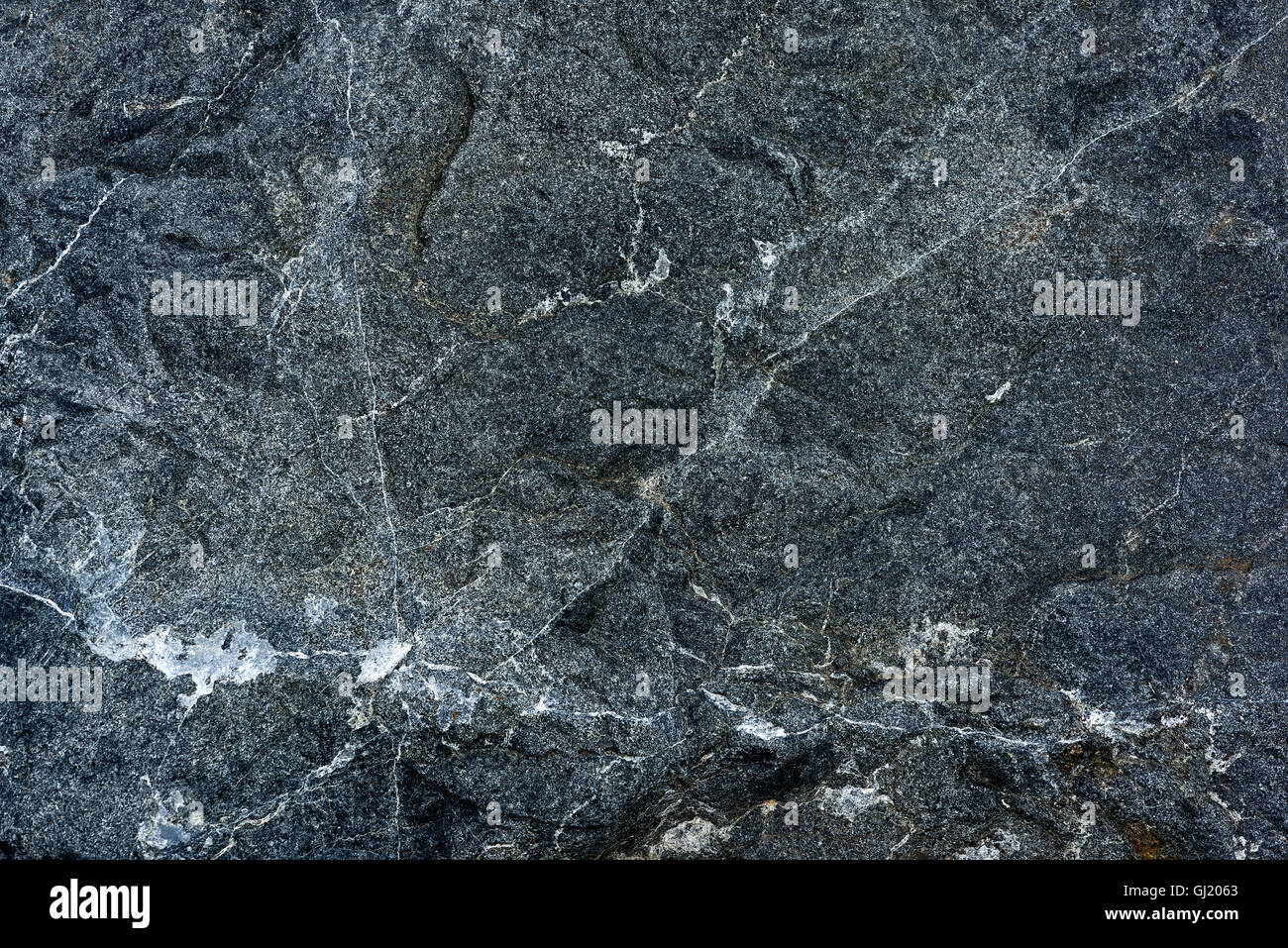 Pattern and texture in close up of fine grained igneous rock with quartz intrusions - Stock Image