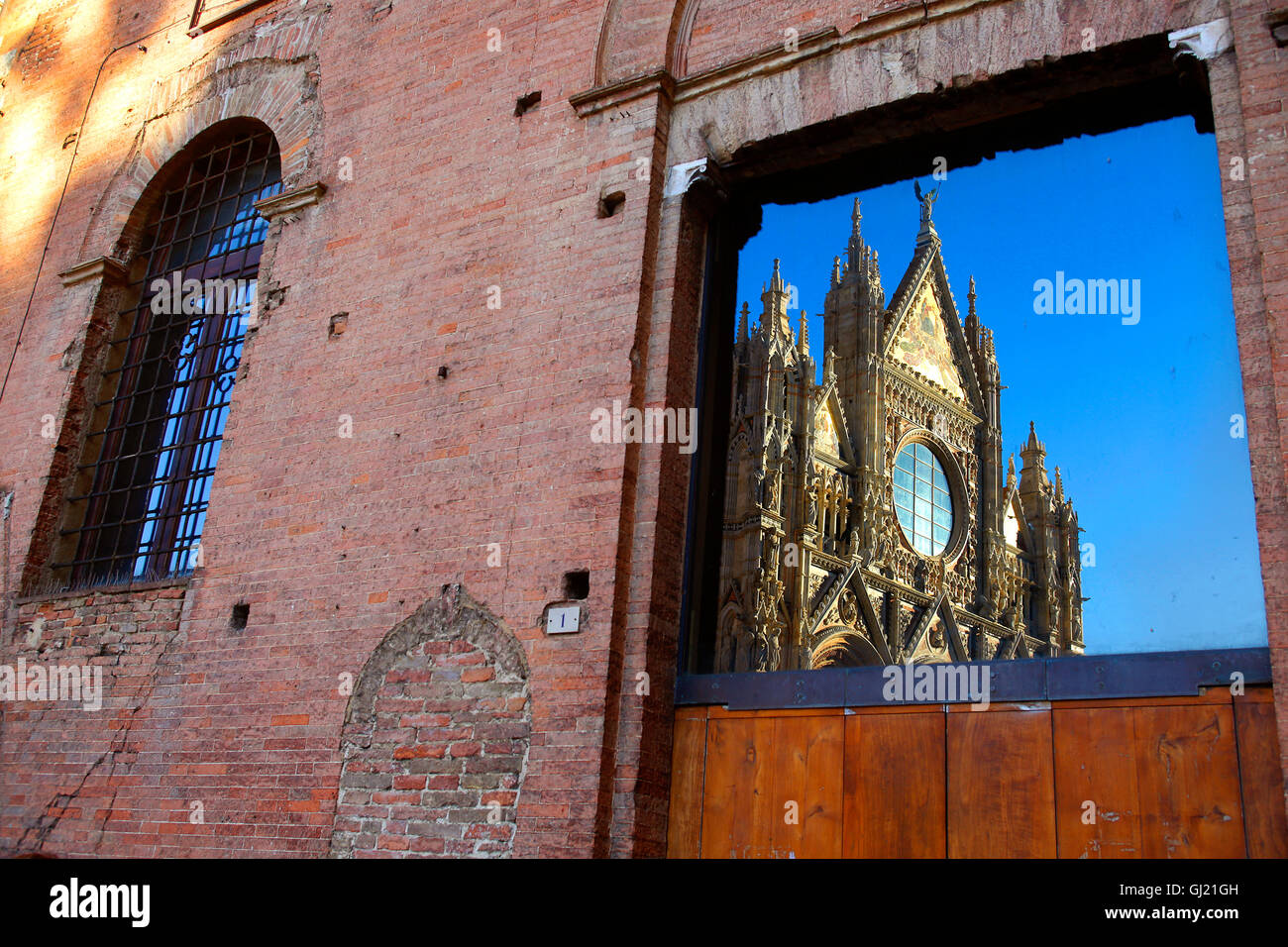 Siena Cathedral or Duomo reflected in a building on the Piazza del Duomo. Stock Photo