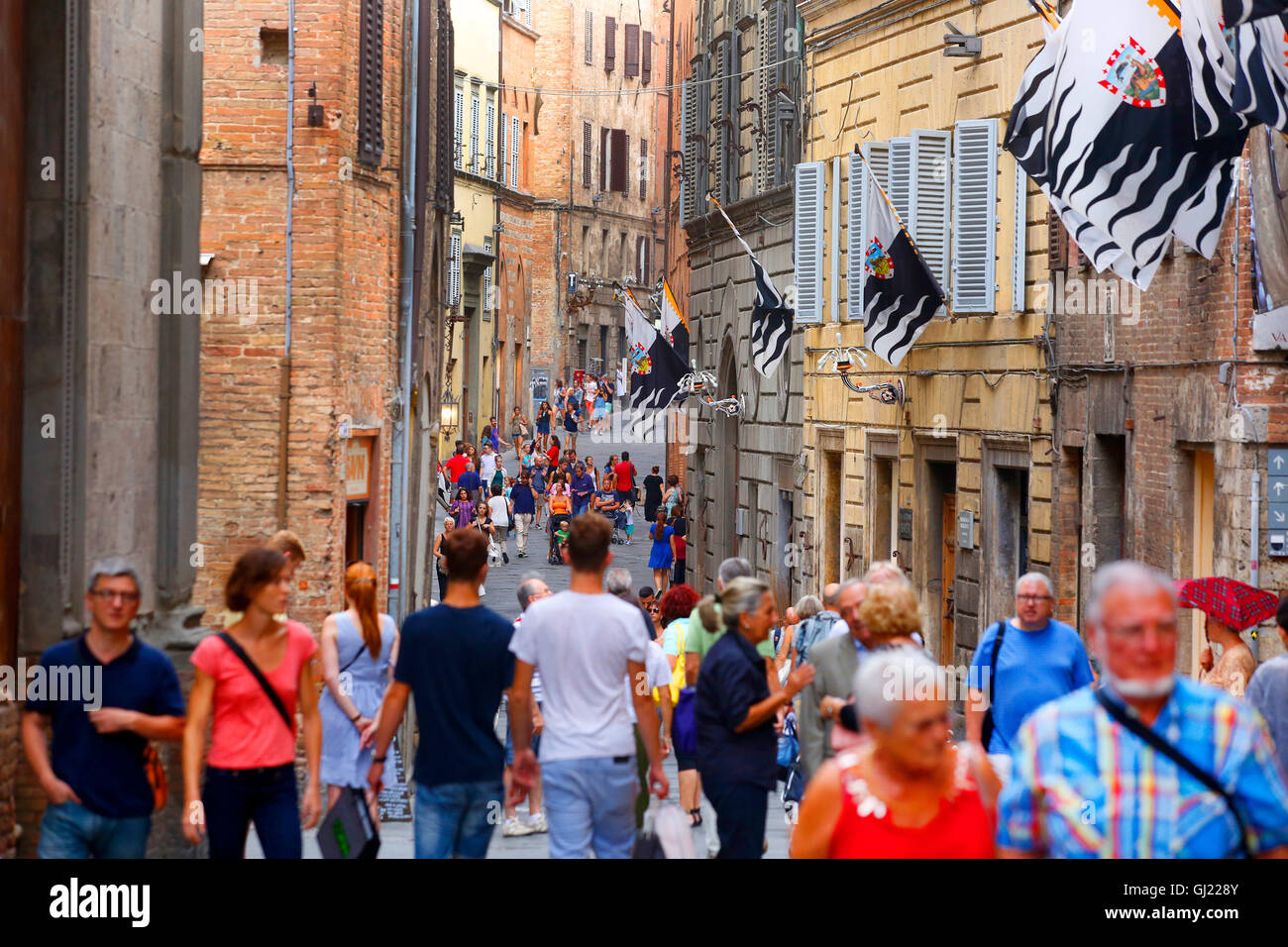 Pedestrians walk along Via Montanini in Siena, Italy. - Stock Image