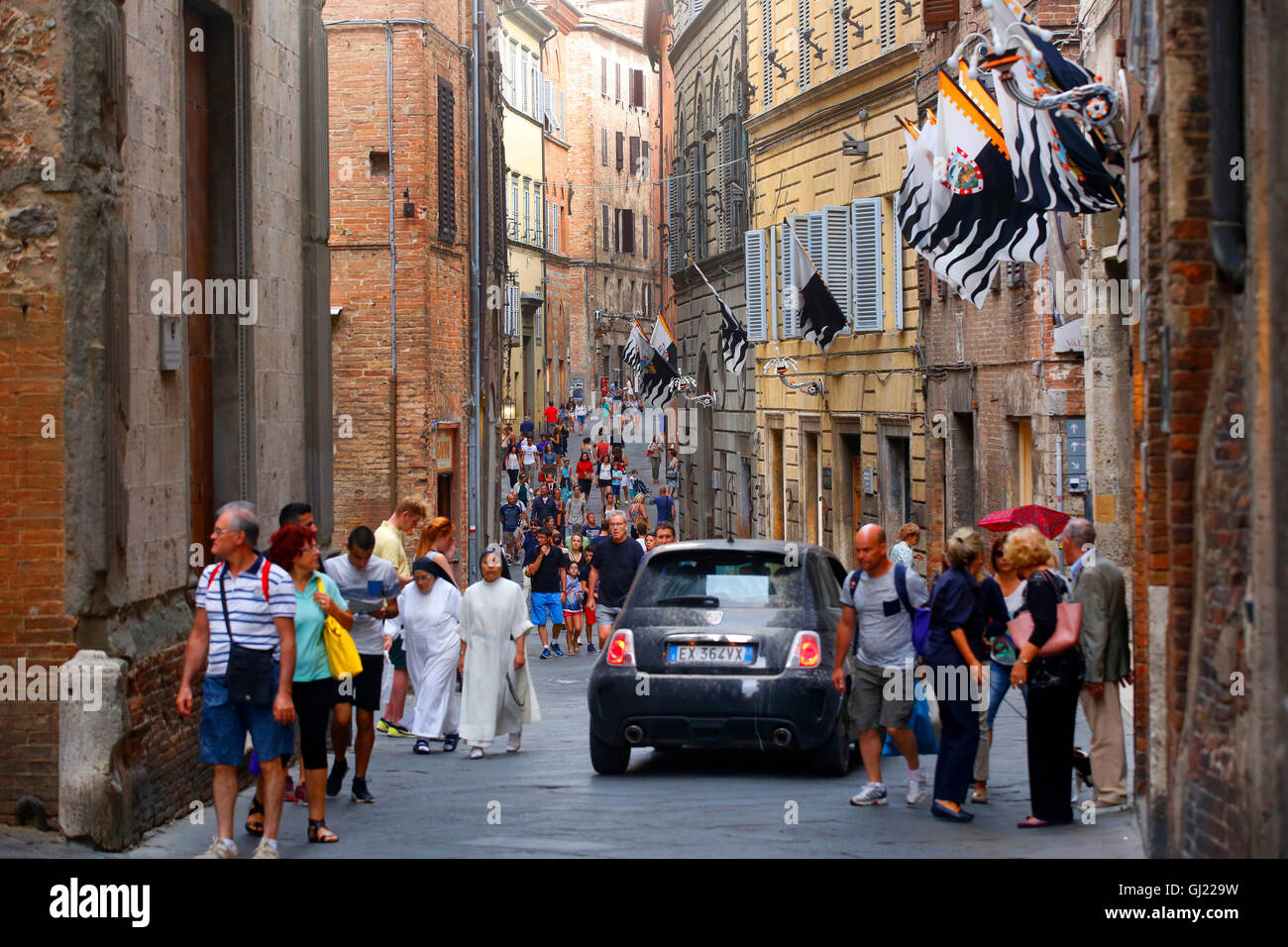 A Fiat 500 makes its way past pedestrians along Via Montanini in Siena, Italy. - Stock Image
