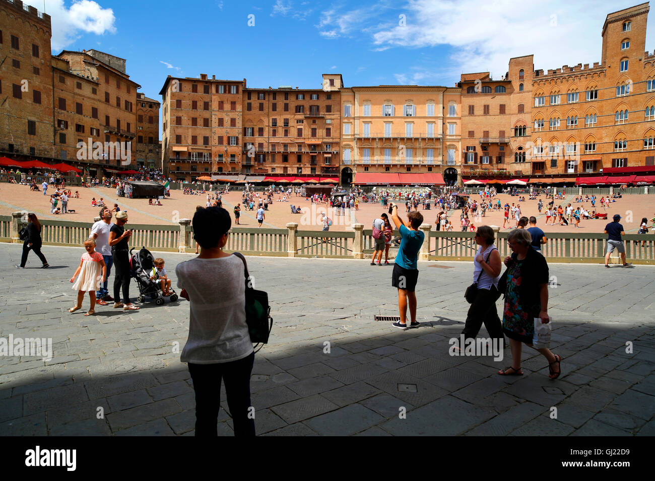 Tourists on the Piazza del Campo, famous for the Il Palio horse race, in Siena, Italy - Stock Image