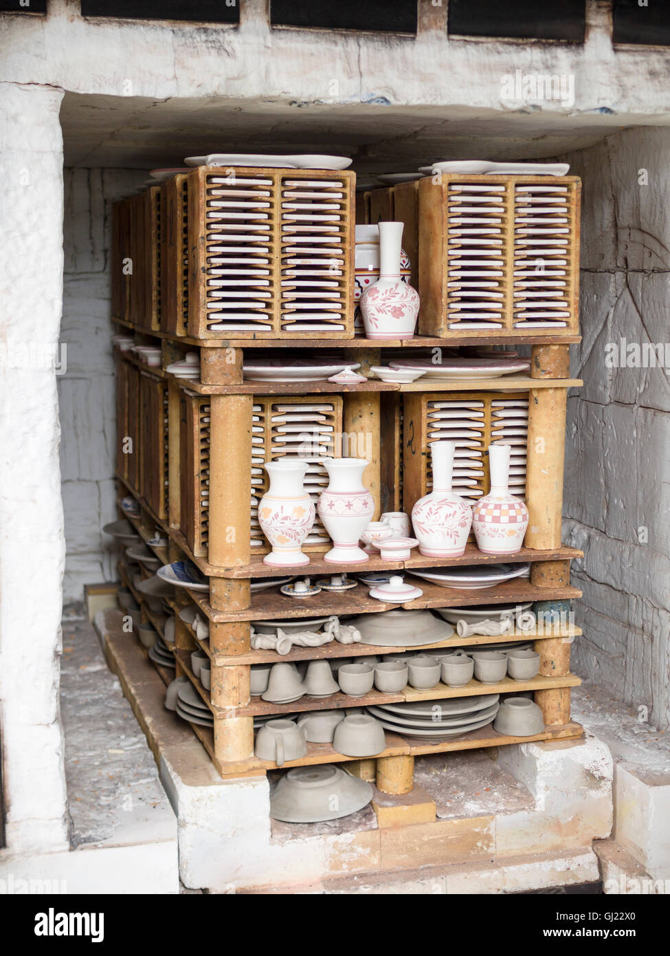 Pottery Ready for Firing. A batch of pottery stacked inside a large furnace ready to be glazed at Ceramic Vieira, - Stock Image