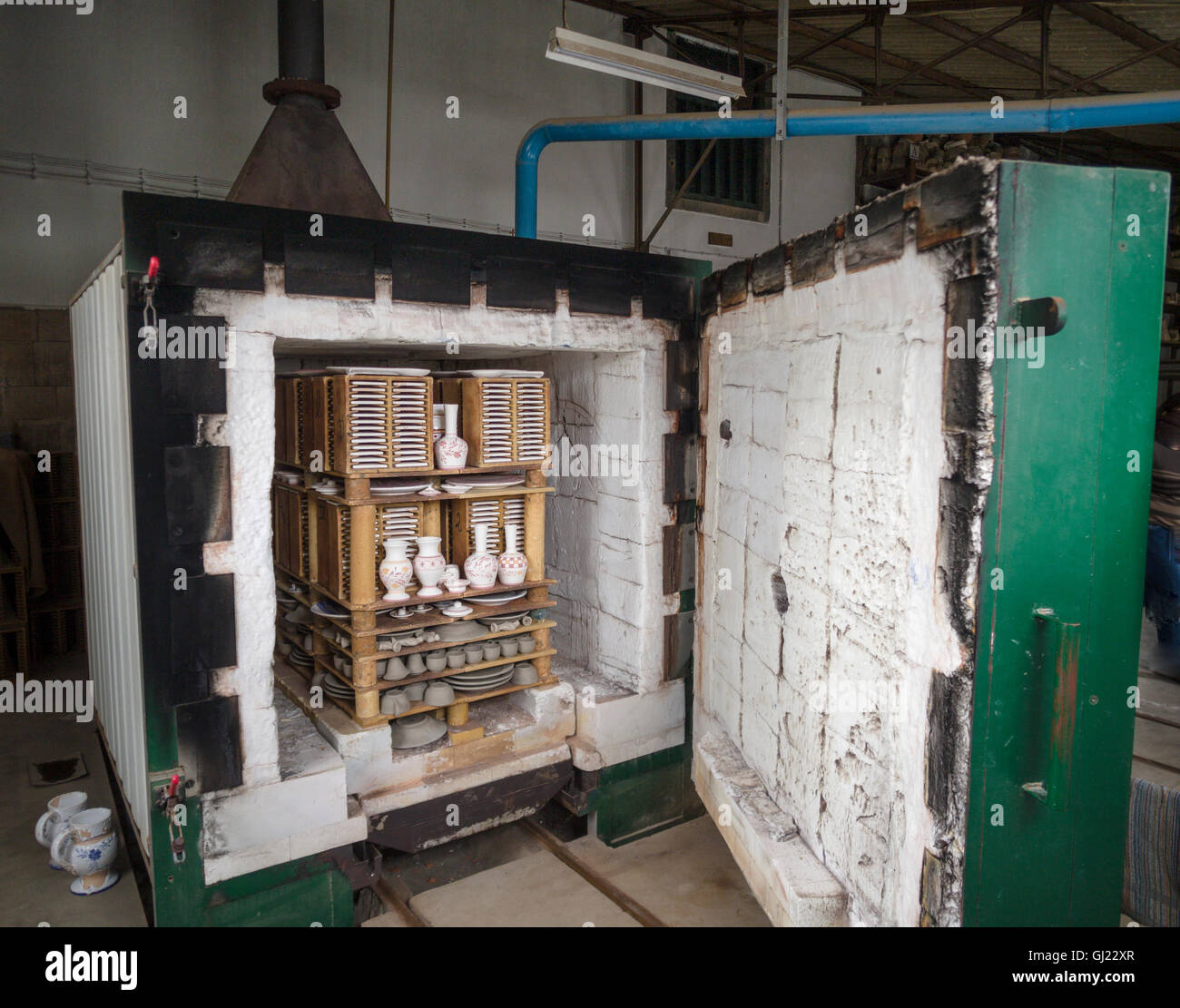 Pottery Furnace/Kiln filled with items to be fired. A batch of pottery stacked inside a large furnace ready to be - Stock Image