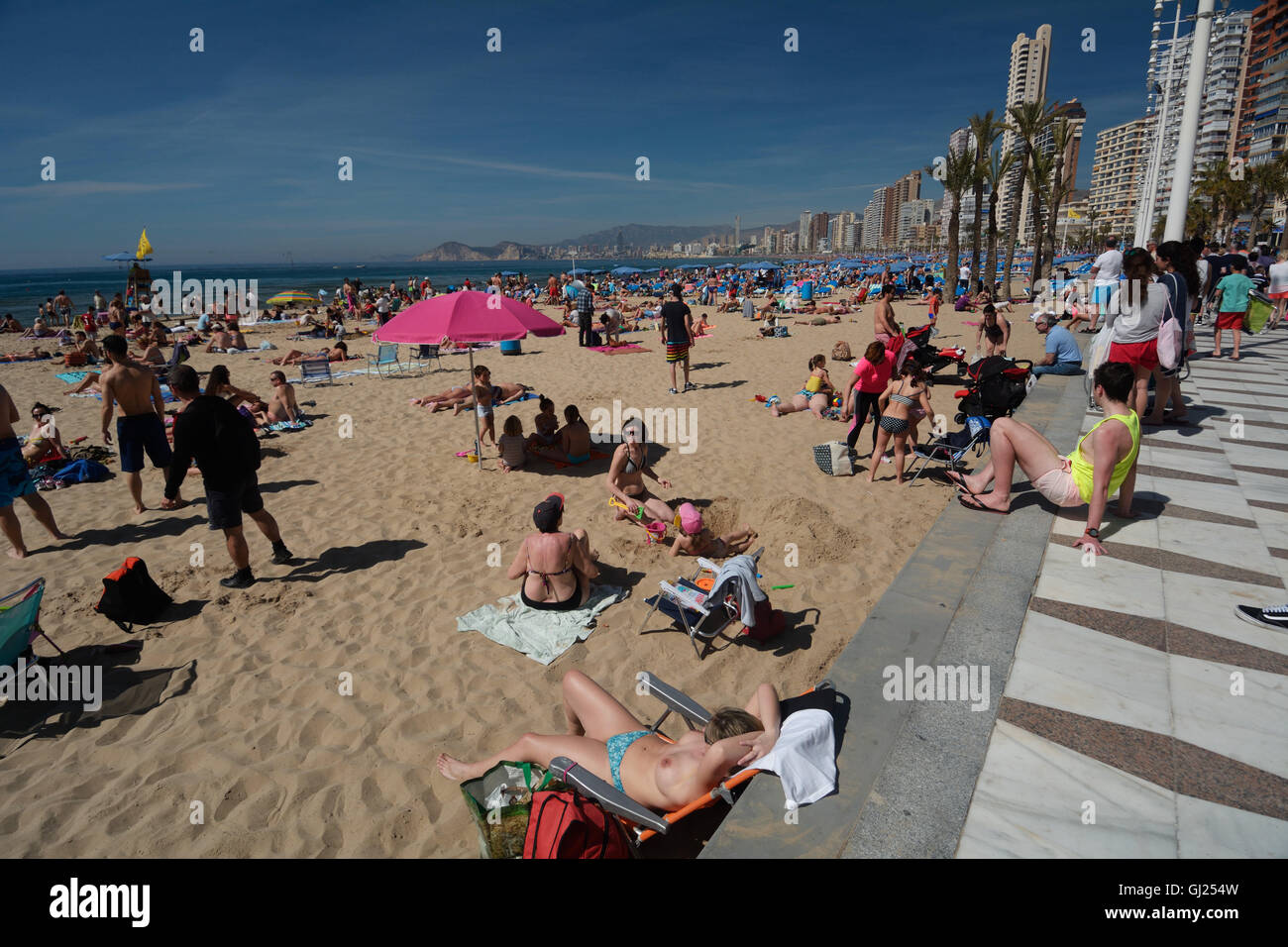 Spain, Benidorm, Levante beach, sunbathers and high-rise buildings in the background - Stock Image