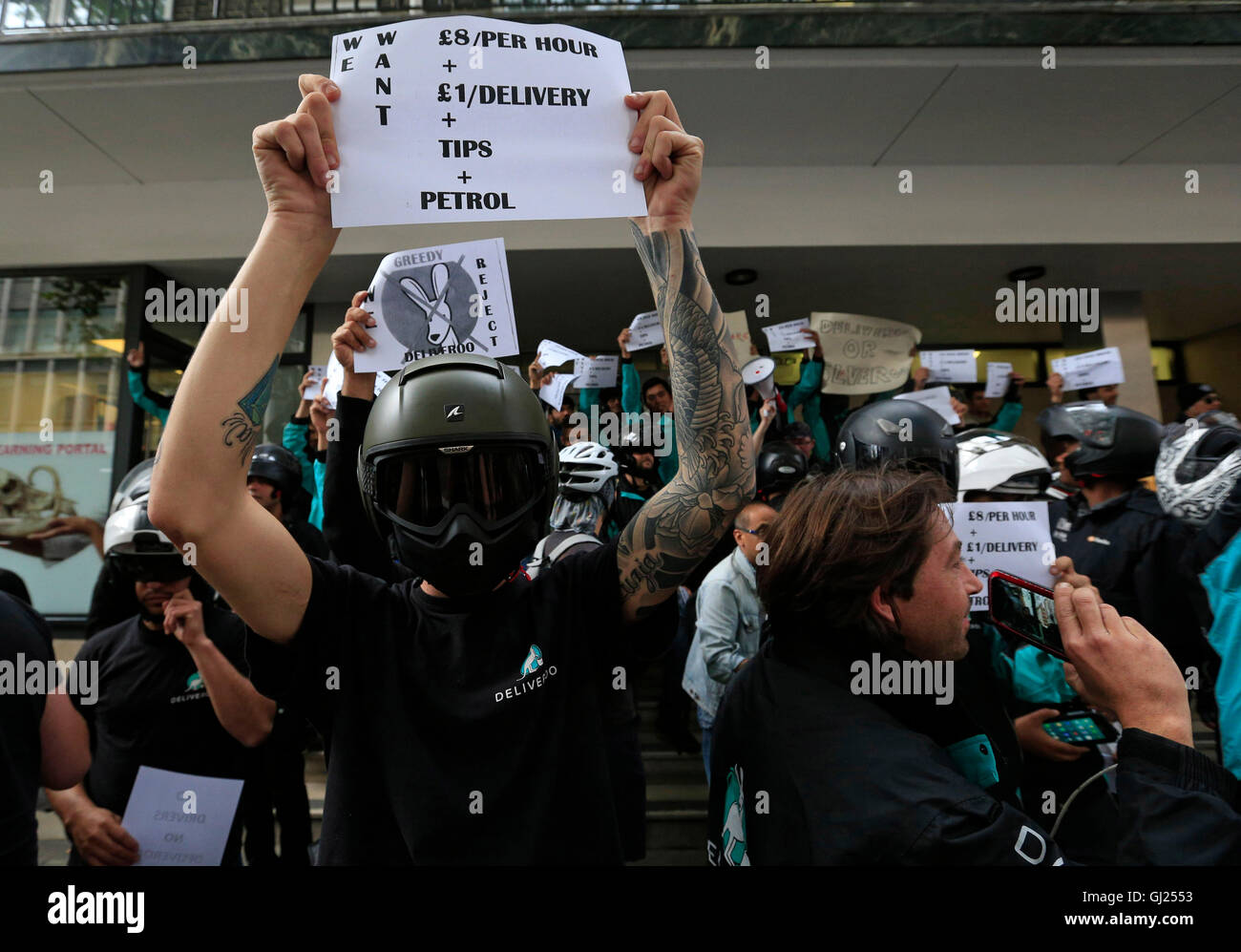 Deliveroo riders hold a protest over pay outside the company HQ in Torrington Place, London. - Stock Image