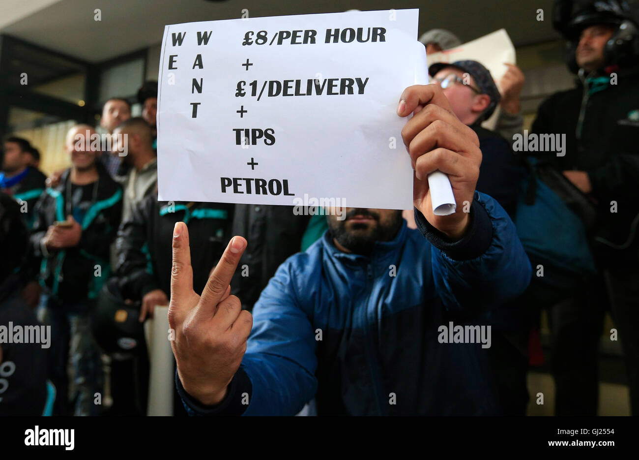 EDITORS NOTE GESTURE Deliveroo riders hold a protest over pay outside the company HQ in Torrington Place, London. - Stock Image