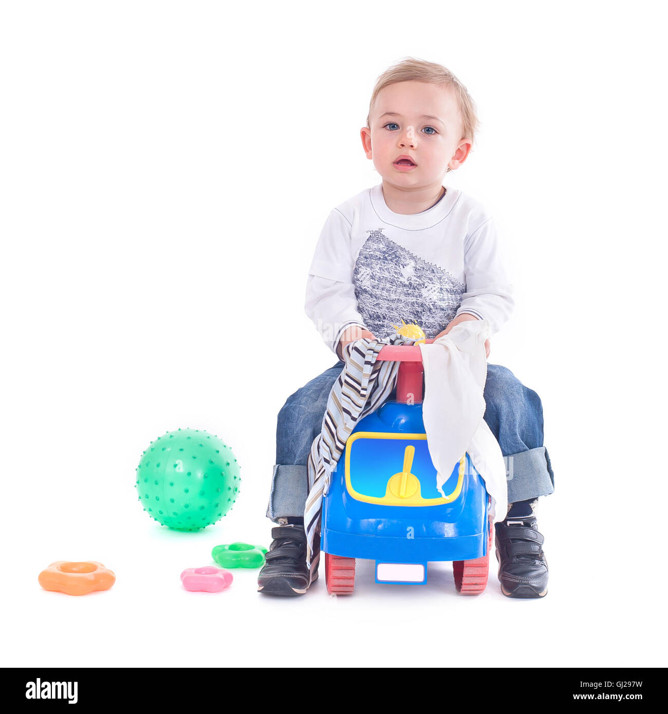 Young boy riding a toy car Stock Photo
