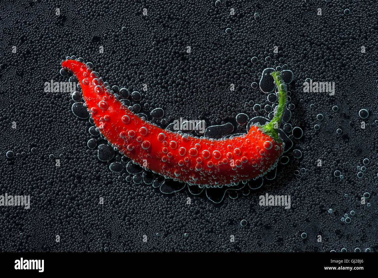 Chili pepper in a mineral water, a series of photos. Close-up carbonated water against black background - Stock Image