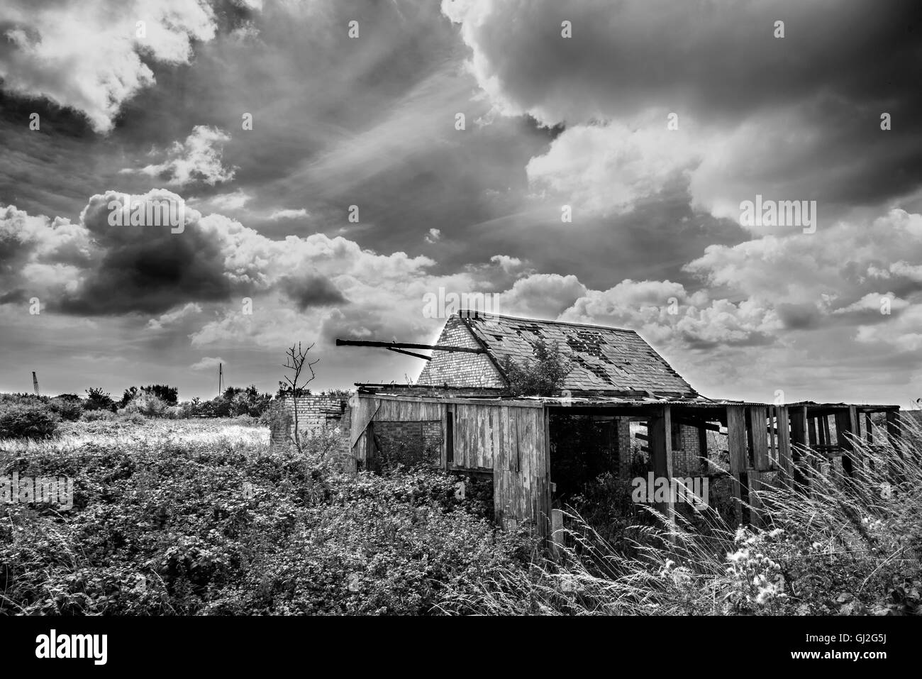 Black and white photograph of a derelict farm in Suffolk with billowing clouds - Stock Image