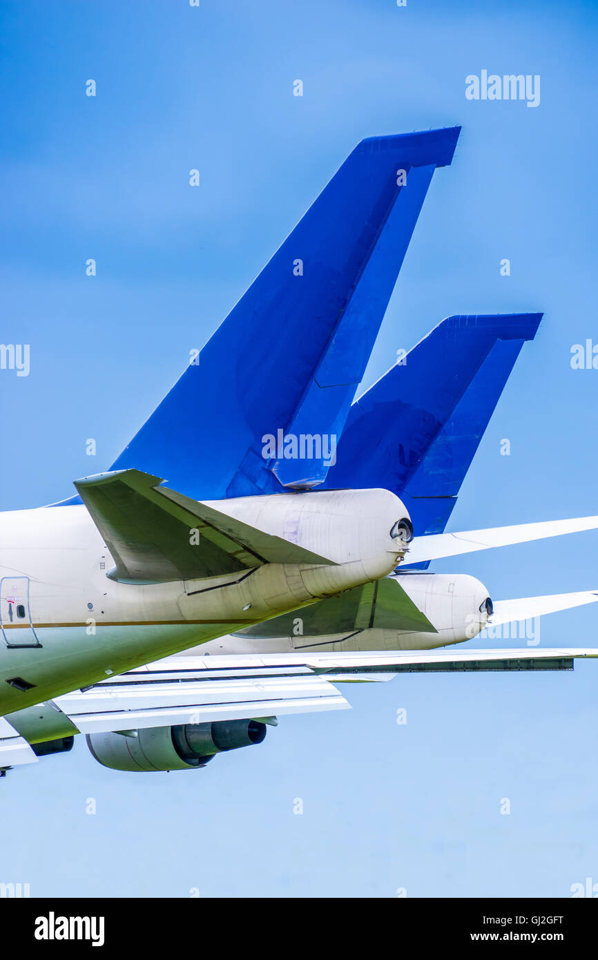 Two blue airliner tail planes parked side by side against a blue sky - Stock Image