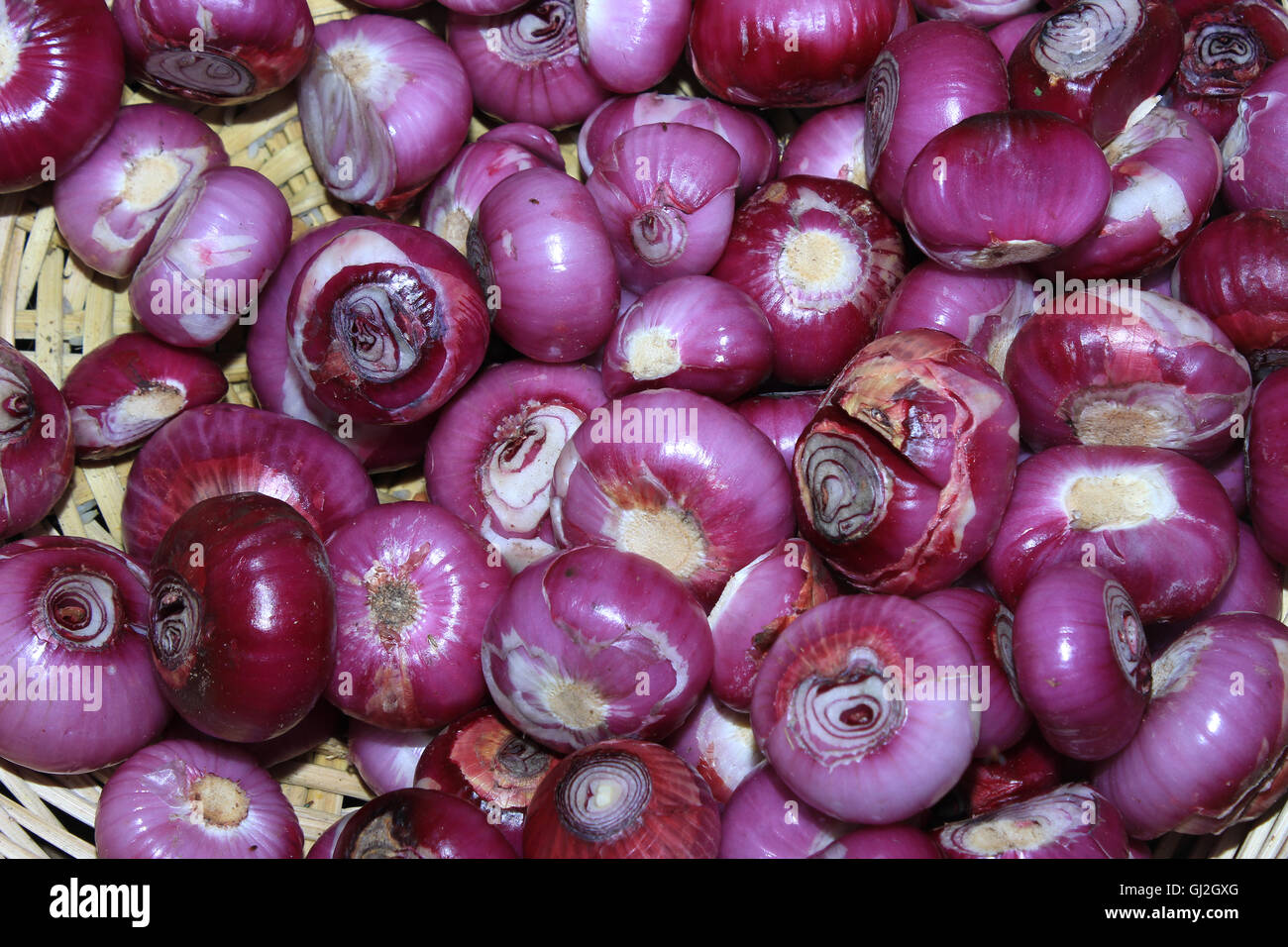 Red onions. Red onions in a basket at a country market after cleaning. - Stock Image