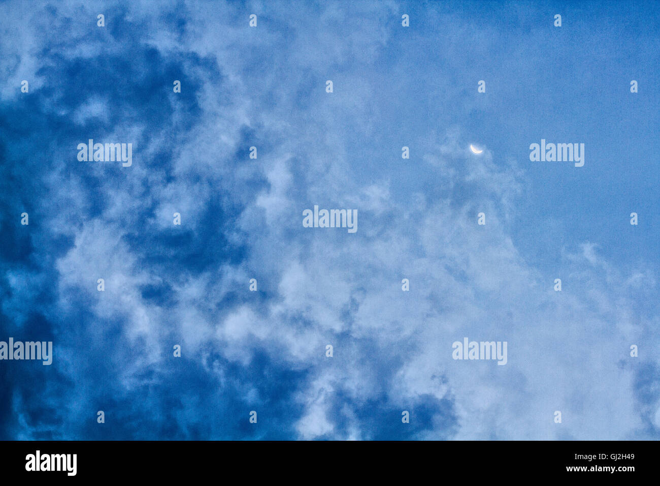 Clouded sky with crescent moon. - Stock Image
